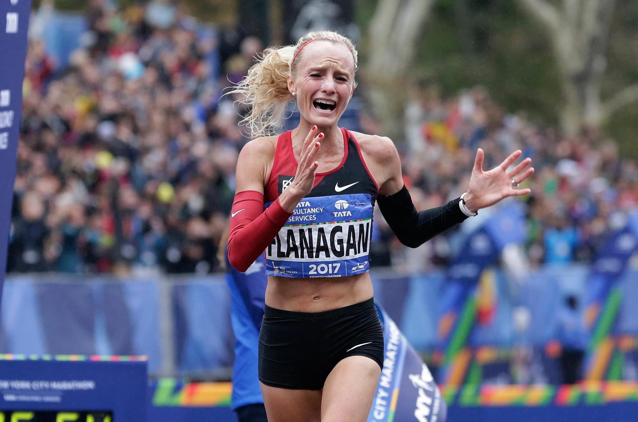 Female runner expressing emotion as she crosses finish line (© AP Images)