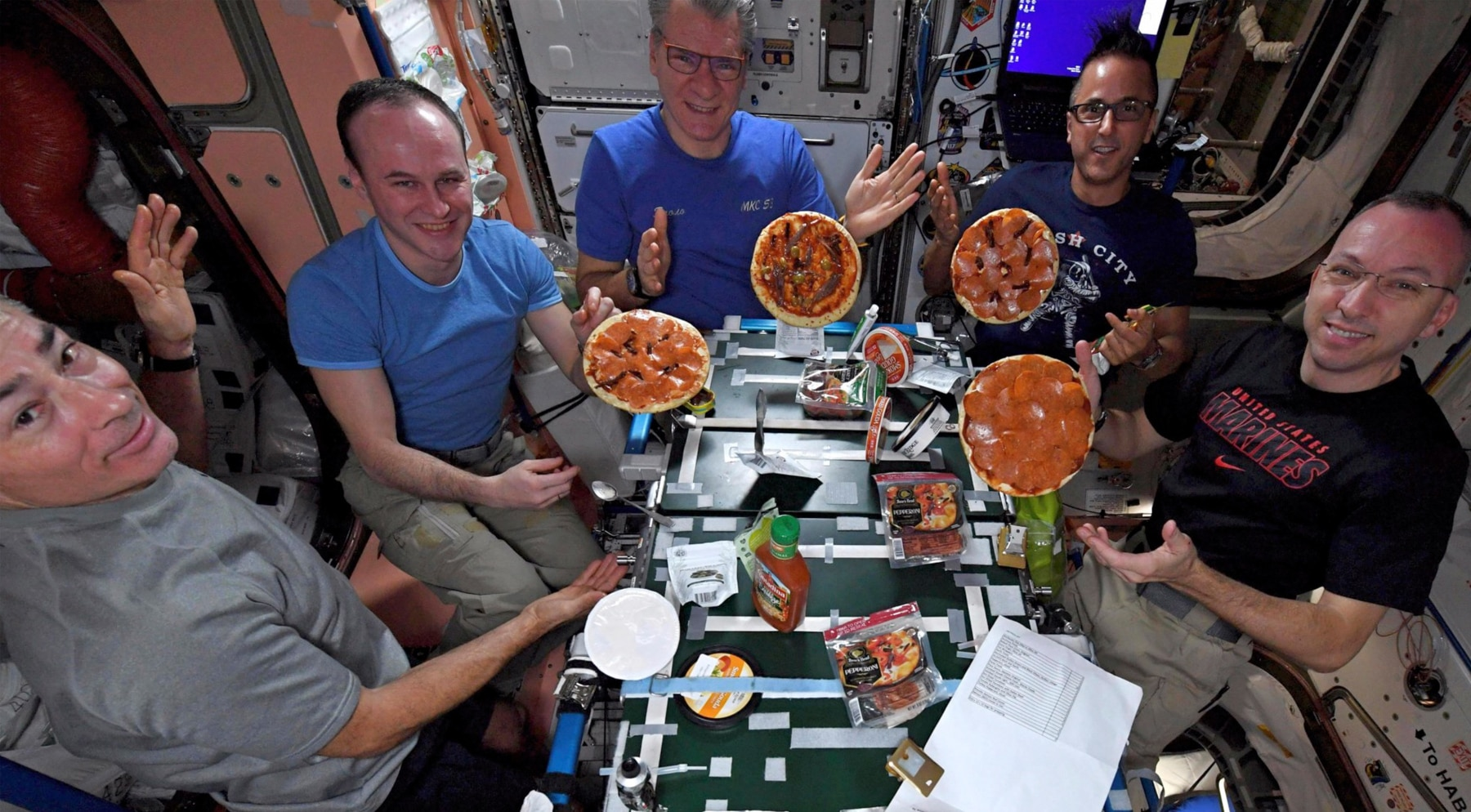 Astronauts showing pizzas floating in air (© AP Images)