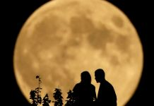 Two people in silhouette sitting with large full moon in the background (© AP Images)