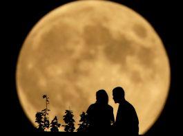 Silhueta de duas pessoas sentadas e, ao fundo, uma enorme lua cheia (© AP Images)