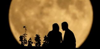 Two people in silhouette sitting with large full moon in the background (©AP Images)