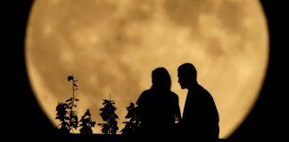 Silueta de dos personas sentadas con una gran luna llena al fondo (© AP Images)