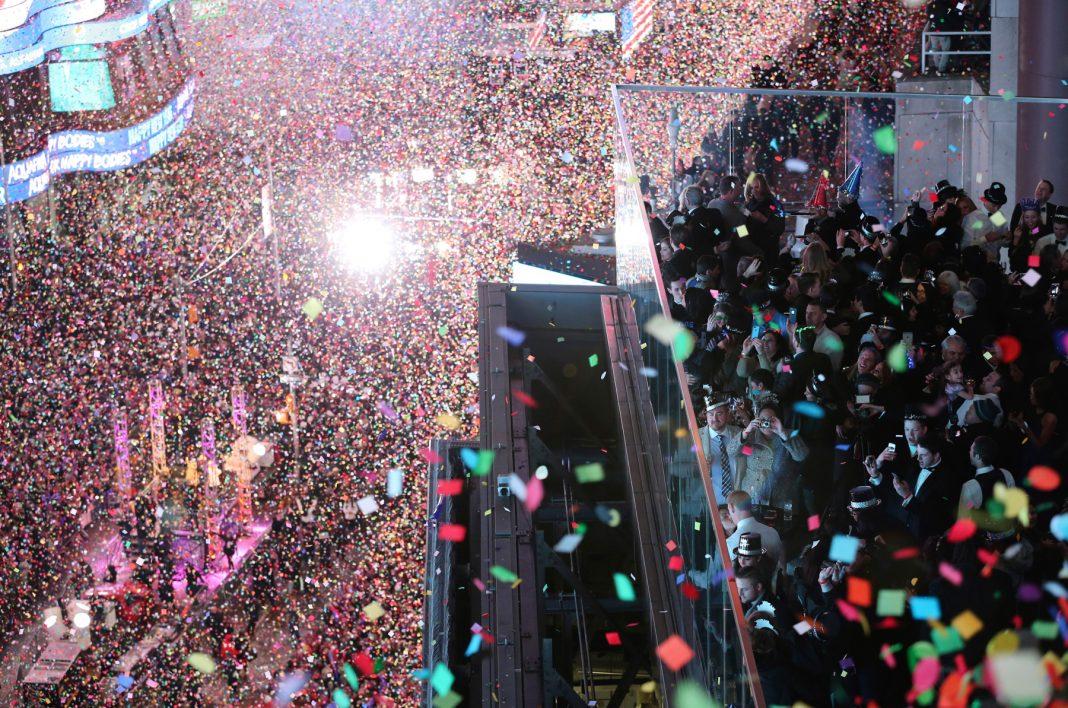 Confeti cayendo sobre una gran multitud de personas (© AP Images)