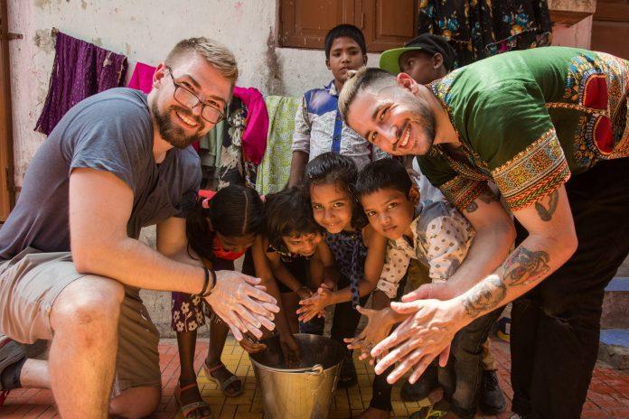 Dois homens e um pequeno grupo de crianças com as mãos juntas sobre um balde (© Bernat Parera)