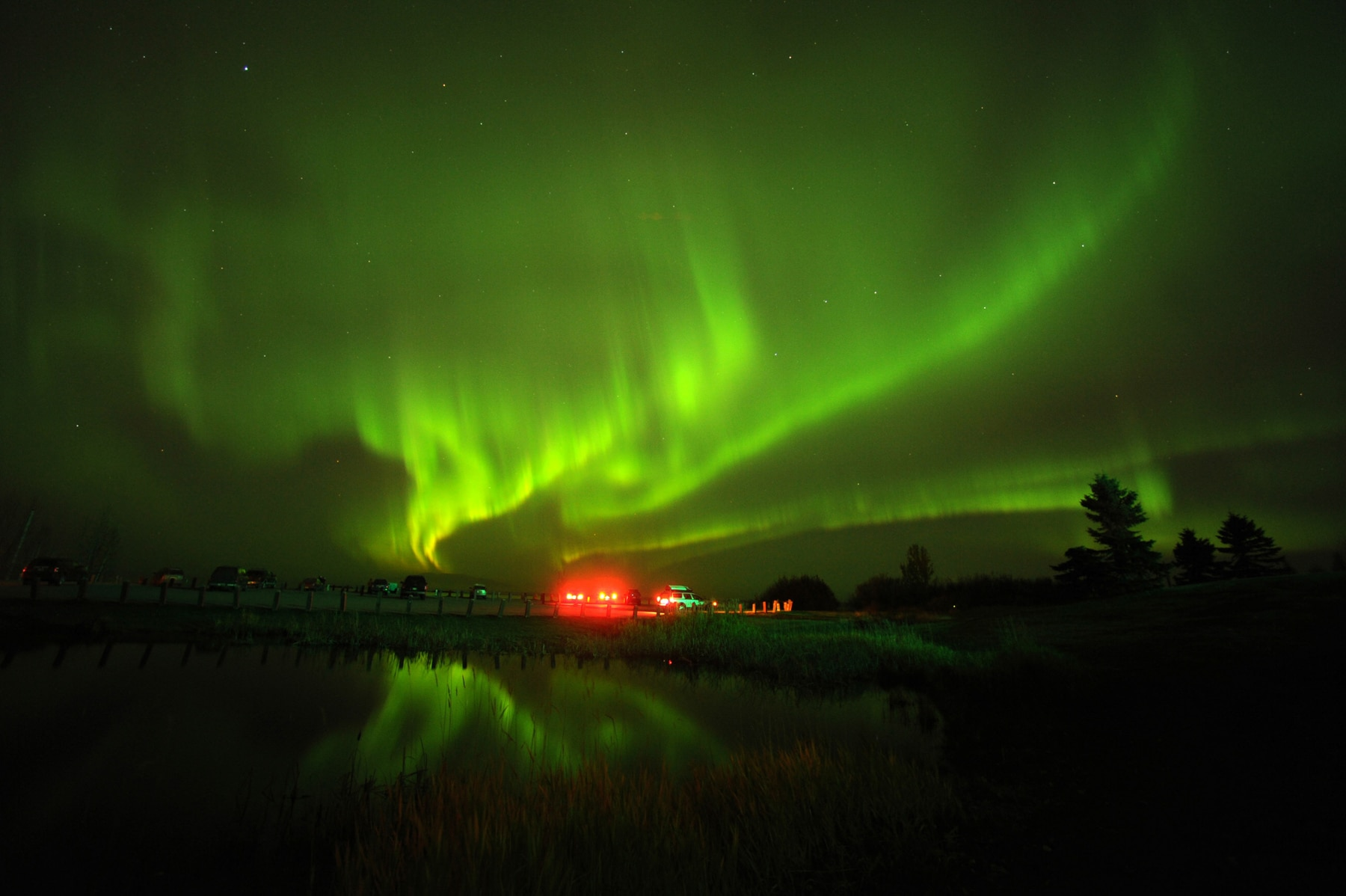 Northern lights making green streaks across a night sky, with a small building glowing red (© Bob Hallinen/Anchorage Daily News/MCT/Getty Images)