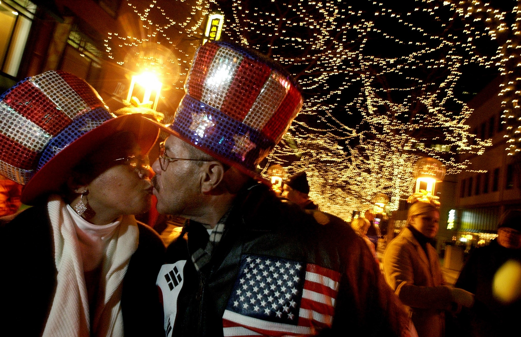 Dos personas con gorros rojo, blanco y azul besándose (© Craig Walker/Denver Post vía Getty Images)