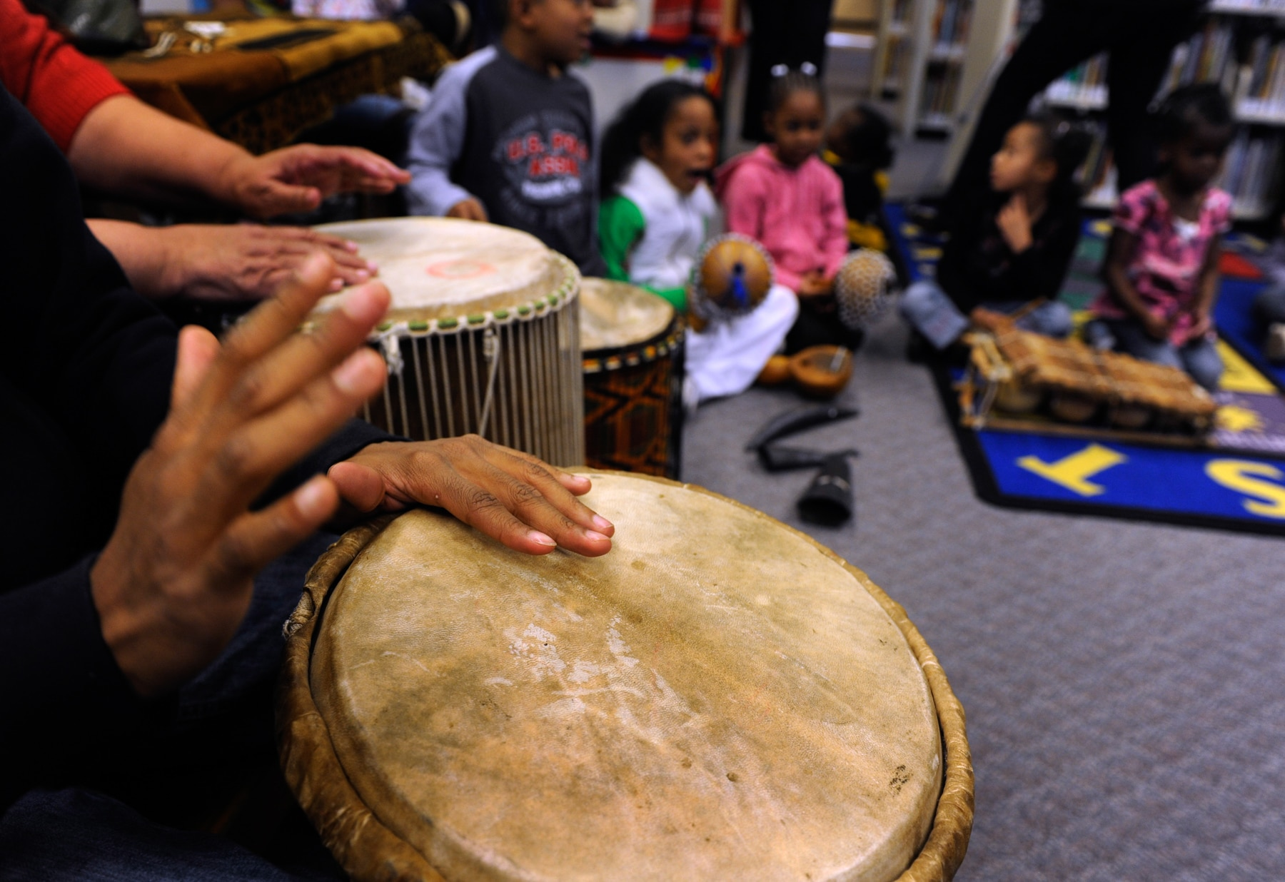 Hands playing drums with children listening in the background (© Kathryn Scott Osler/The Denver Post via Getty Images)