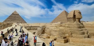 People looking at Great Sphinx and pyramids (© Alan Tsai/Getty Images)