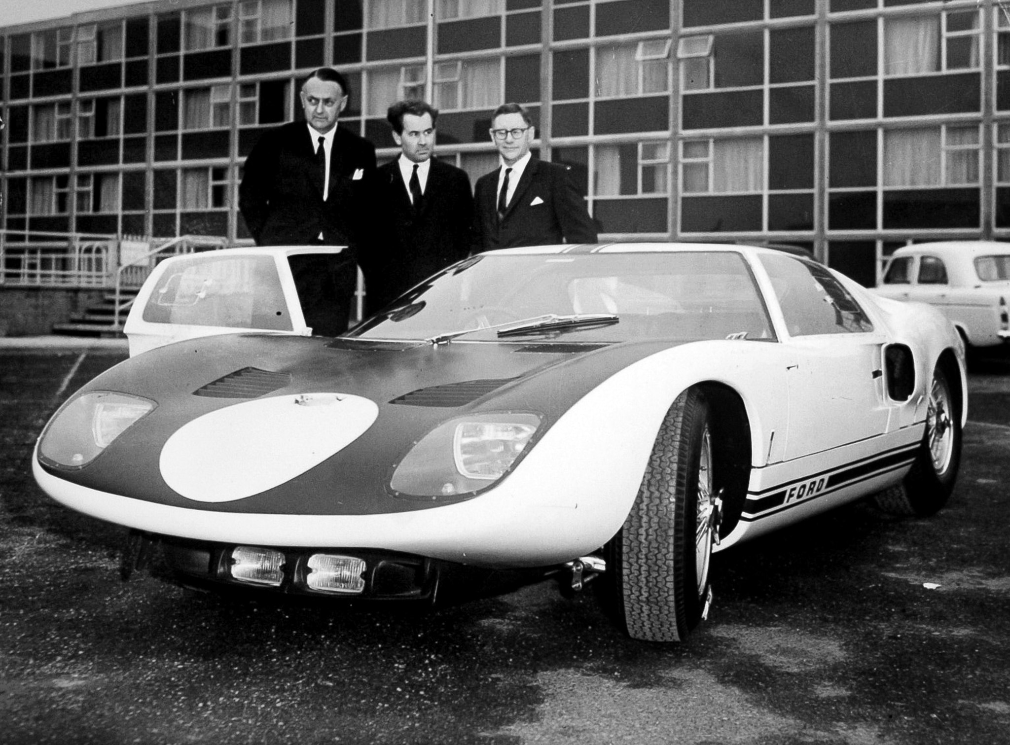Three men in suits standing by sports car (© S&G/PA Images/Getty Images)