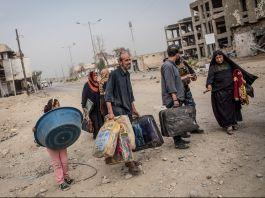 Un petit groupe de personnes avec des bagages marchant dans une rue bombardée (© Chris McGrath/Getty Images)