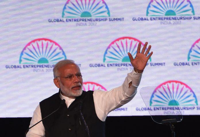 Indian Prime Minister Narendra Modi waving his arm (© Money Sharma/AFP via Getty Images)