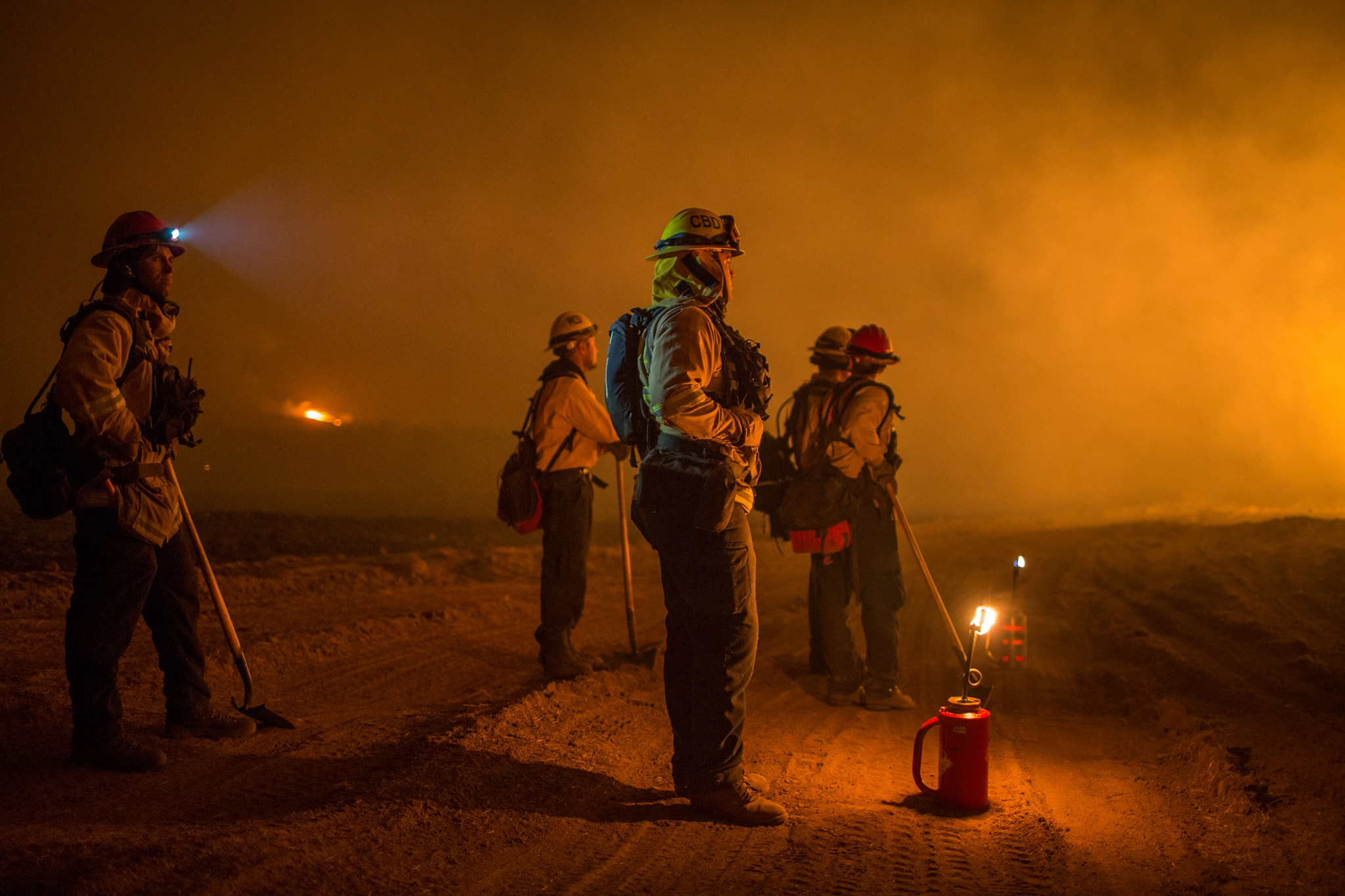 Firefighters looking into distance in orange glow of fire (© David McNew/Getty Images)