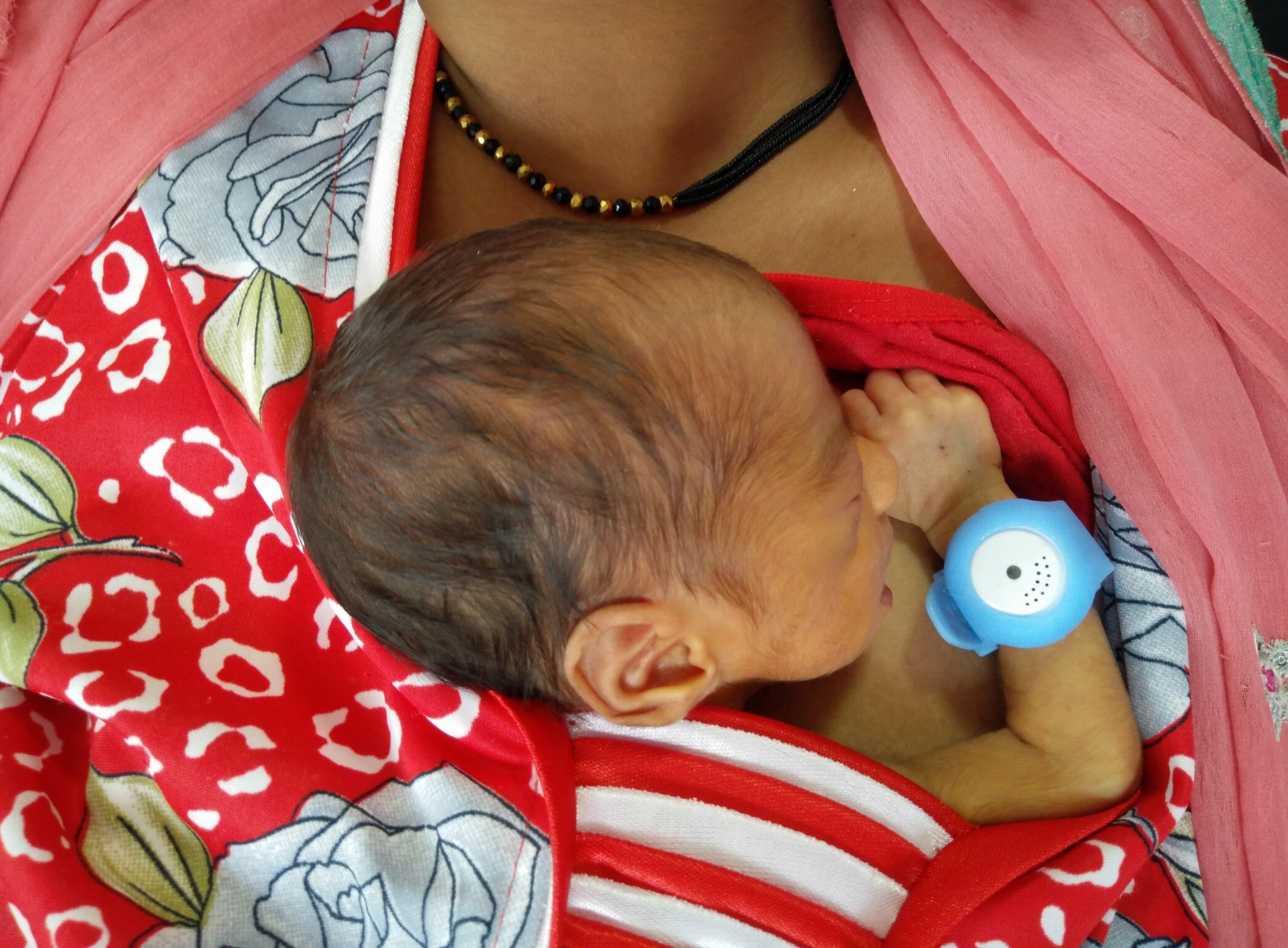 Baby wearing medical bracelet nestling to mother's chest (Bempu)