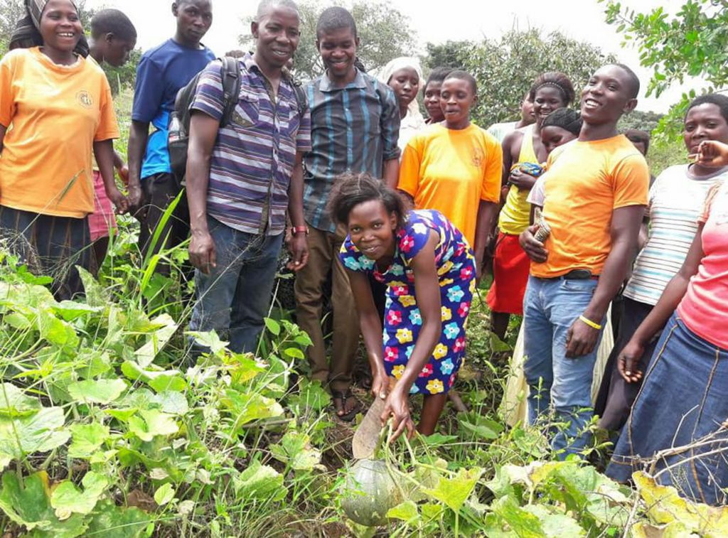 People standing around pumpkin patch (Byeffe Foods via USAID)