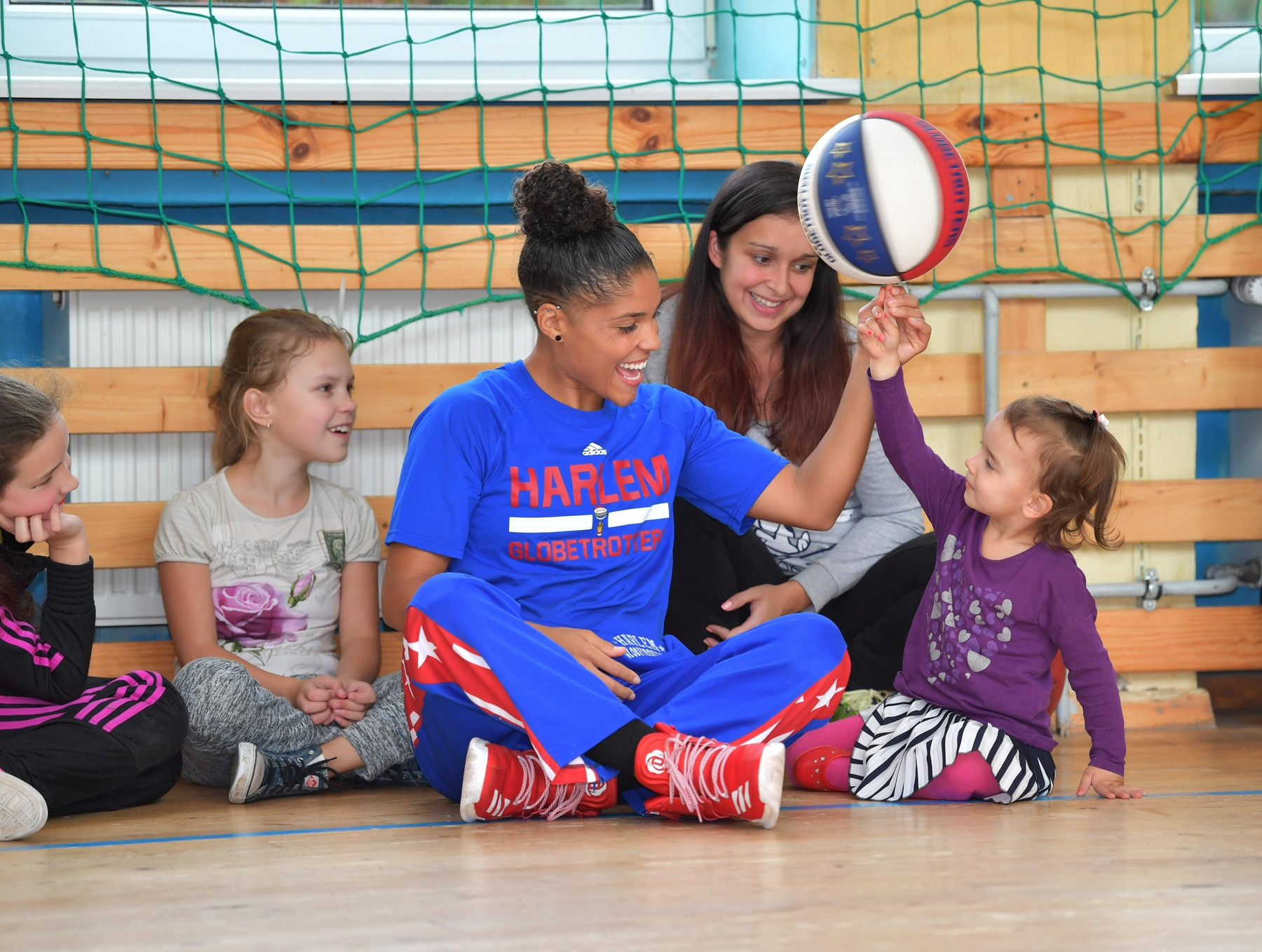 Basketball player sitting on floor with children, spinning a basketball on a young girl's finger (© Brett Meister/Harlem Globetrotters)