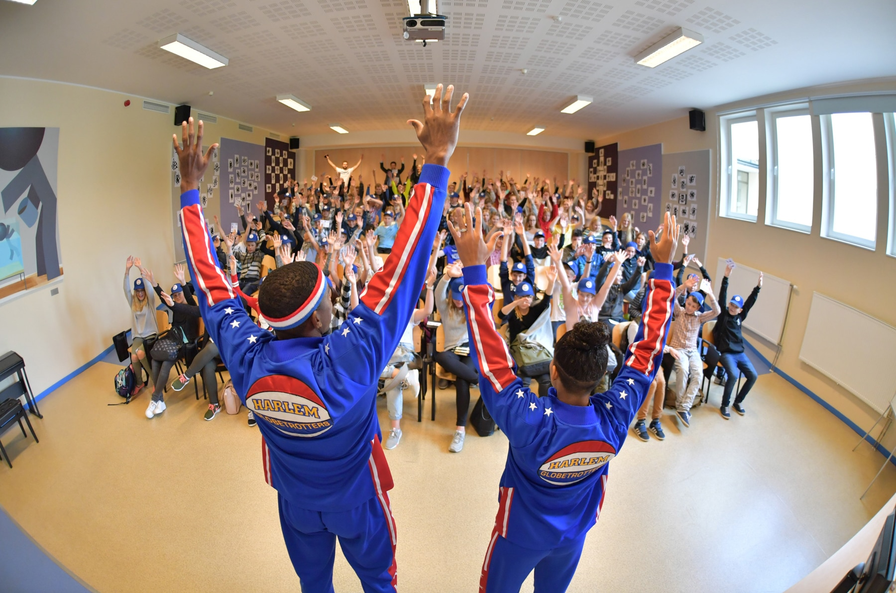 Two adults leading a roomful of students as they raise their arms in victory (© Brett Meister/Harlem Globetrotters)