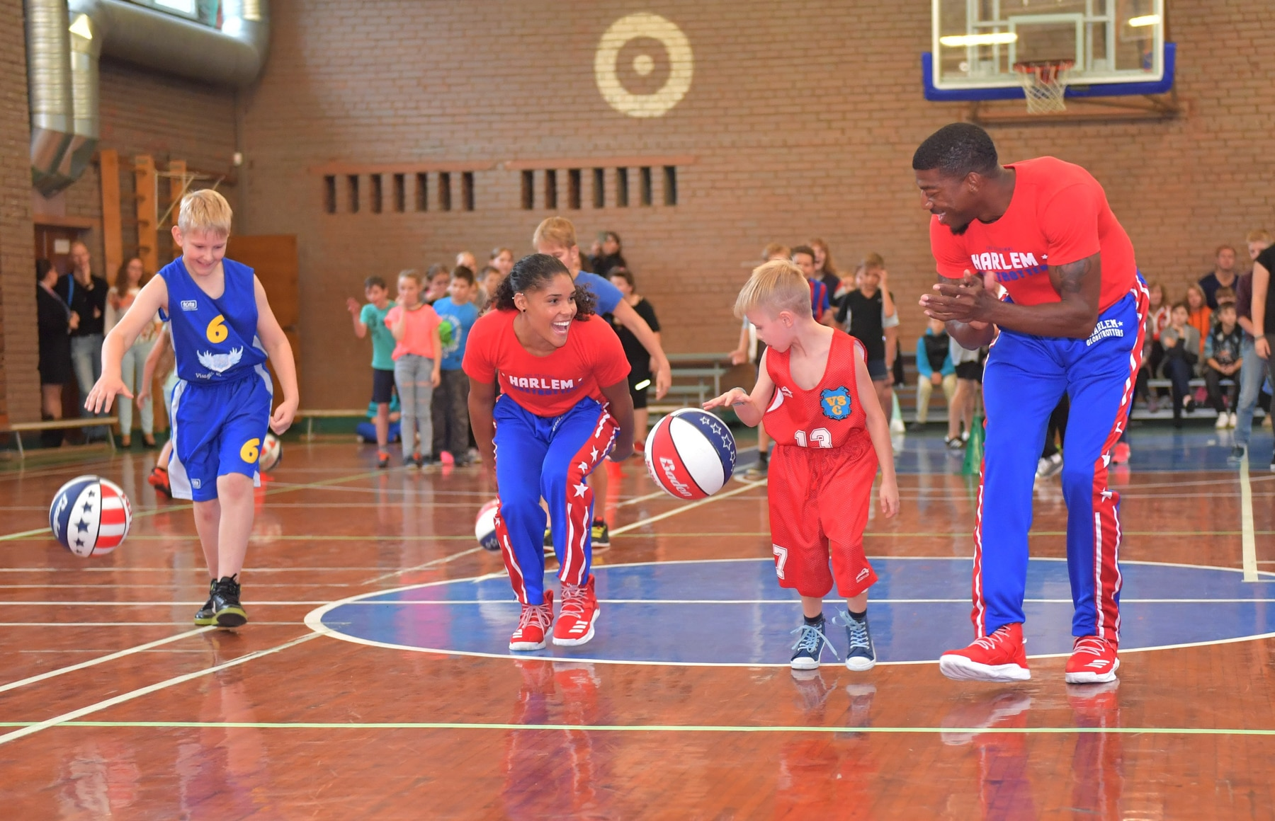 Harlem Globetrotters basketball players dribbling the ball down the court with young children (© Brett Meister/Harlem Globetrotters)