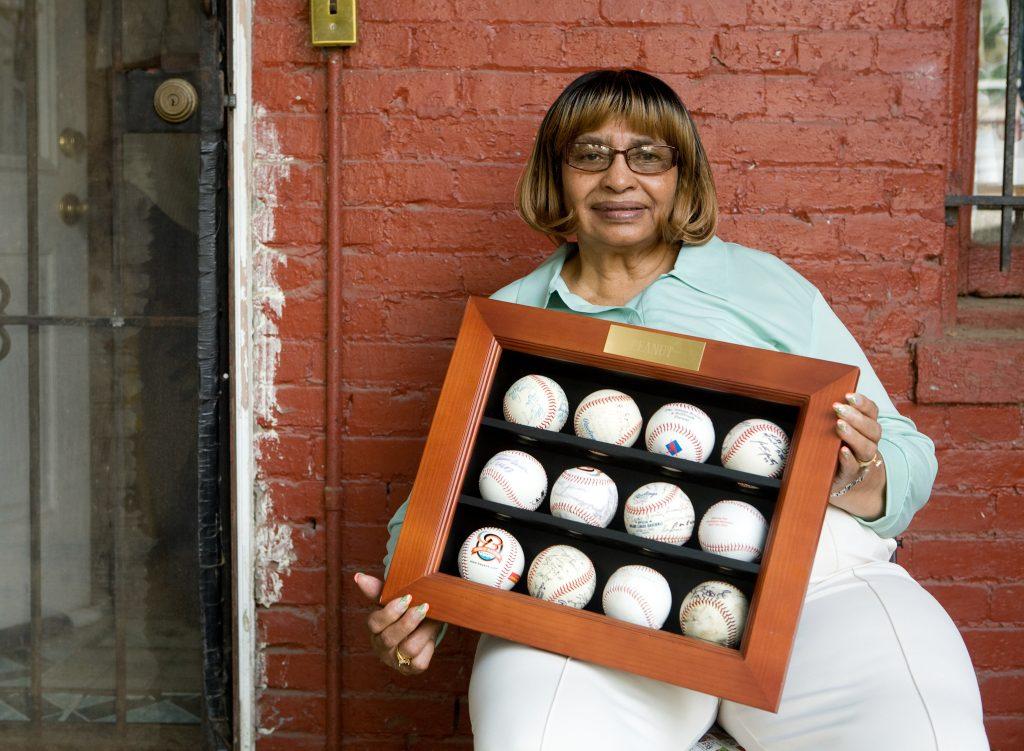 Woman holding framed set of baseballs (© Eli Meir Kaplan/New York Times/Redux)