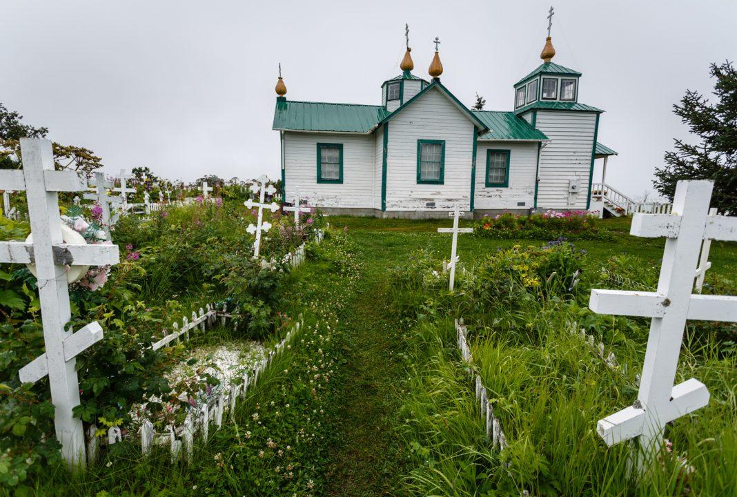 Cruzes ortodoxas russas de pé em um campo na frente de uma igreja (Shutterstock)