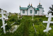 Russian Orthodox crosses standing in a field in front of a church (Shutterstock)