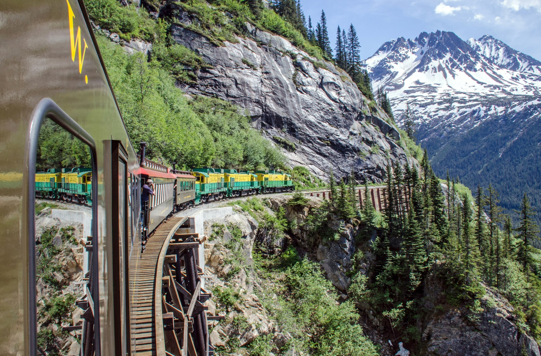 Train traveling along steep Alaska mountainside, with snowy mountain in background (© Shutterstock)