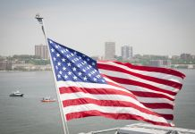 Flag flying with city skyline in background (Shutterstock)
