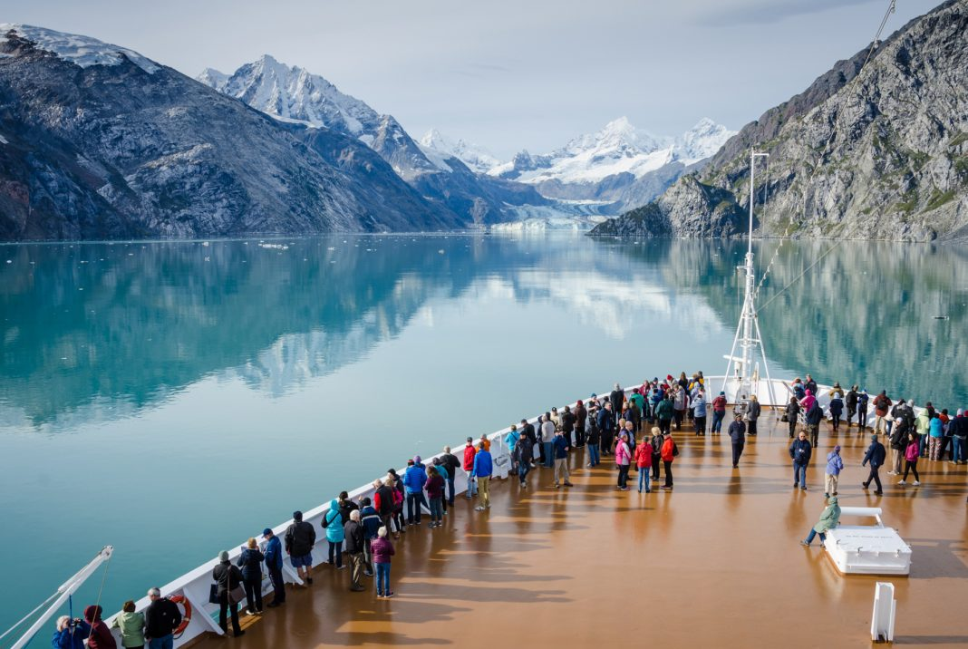 Passengers on deck watching as cruise ship sails into clear bay surrounded by mountains (Shutterstock)