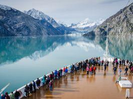 ركاب على سطح سفينة سياحية يتمتعون بمشهد الطبيعة وأنهار الجليد في ألاسكا بينما تبحر السفينة المحاطة بالجبال في المياه الصافية (Shutterstock)