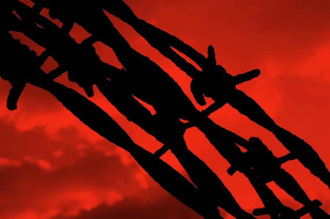 Barbed wire silhouette in front of a blood red sky (Shutterstock)