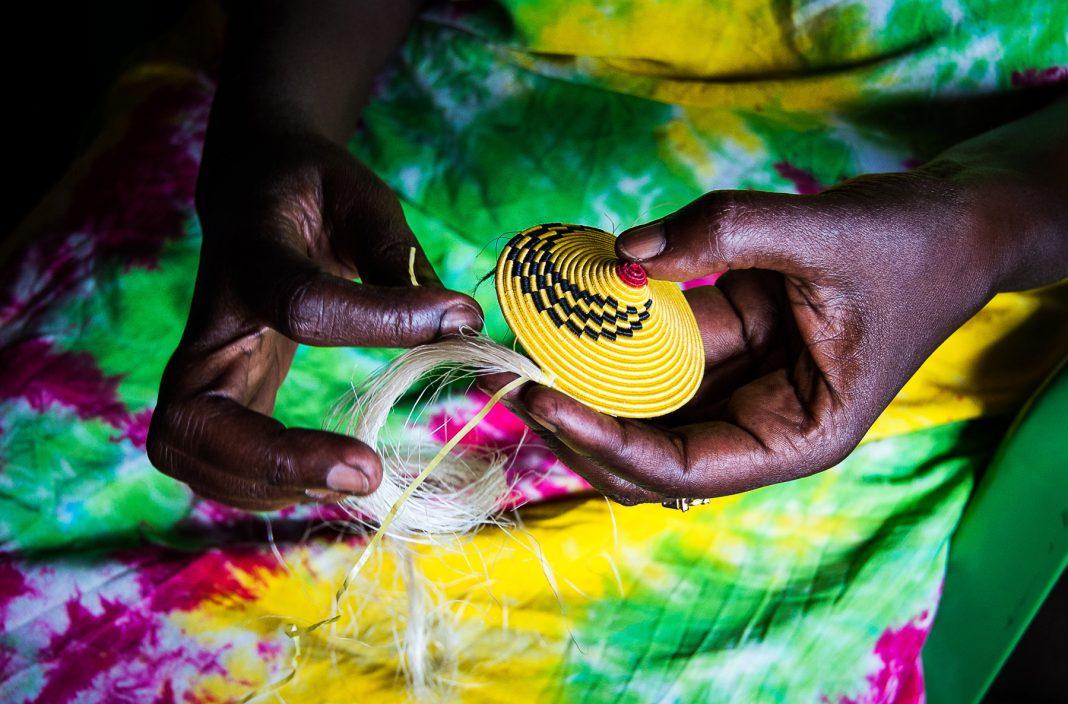 Les mains d'une Africaine en train de tresser des fibres jaunes (Shutterstock)