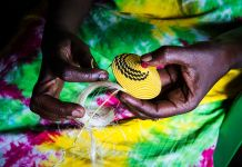 African woman's hands weaving yellow basket (Shutterstock)