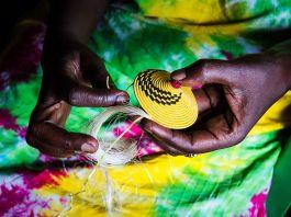 African woman's hands weaving yellow basket (Shutterstock)