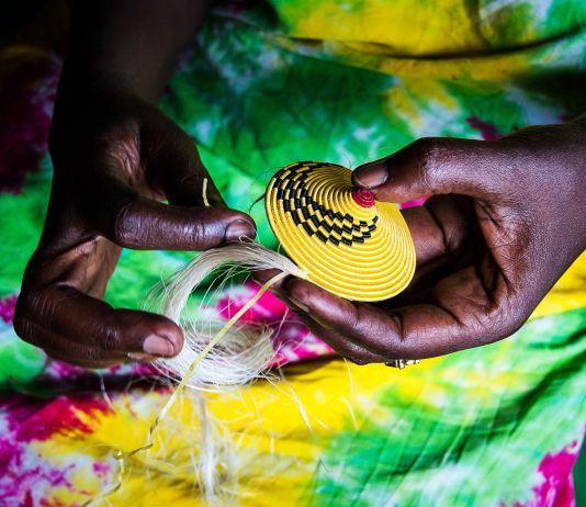 Mãos de mulher africana tecendo cesta amarela (Shutterstock)