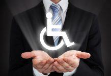 Torse d'un homme en costume faisant une coupe avec ses deux mains sous un logo représentant un fauteuil roulant (Shutterstock)