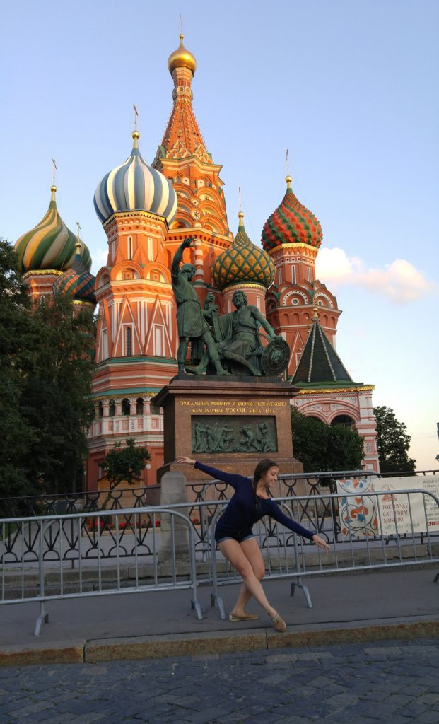 Girl doing ballet pose in front of statue and ornate building (Courtesy of Catherine Cata)