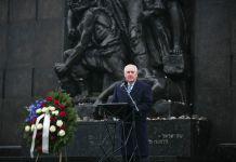 Rex Tillerson ante un atril frente a una gran estatua de granito negro (Depto. de Estado)