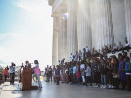 Girl speaking at lectern in front of large group of people at the Lincoln Memorial (State Dept.)