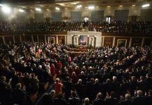Persona pronuncia un discurso en un gran salón repleto de gente (© AP Images)