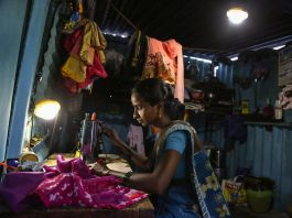 Woman sitting in dimly lit shanty room sewing (© AP Images)