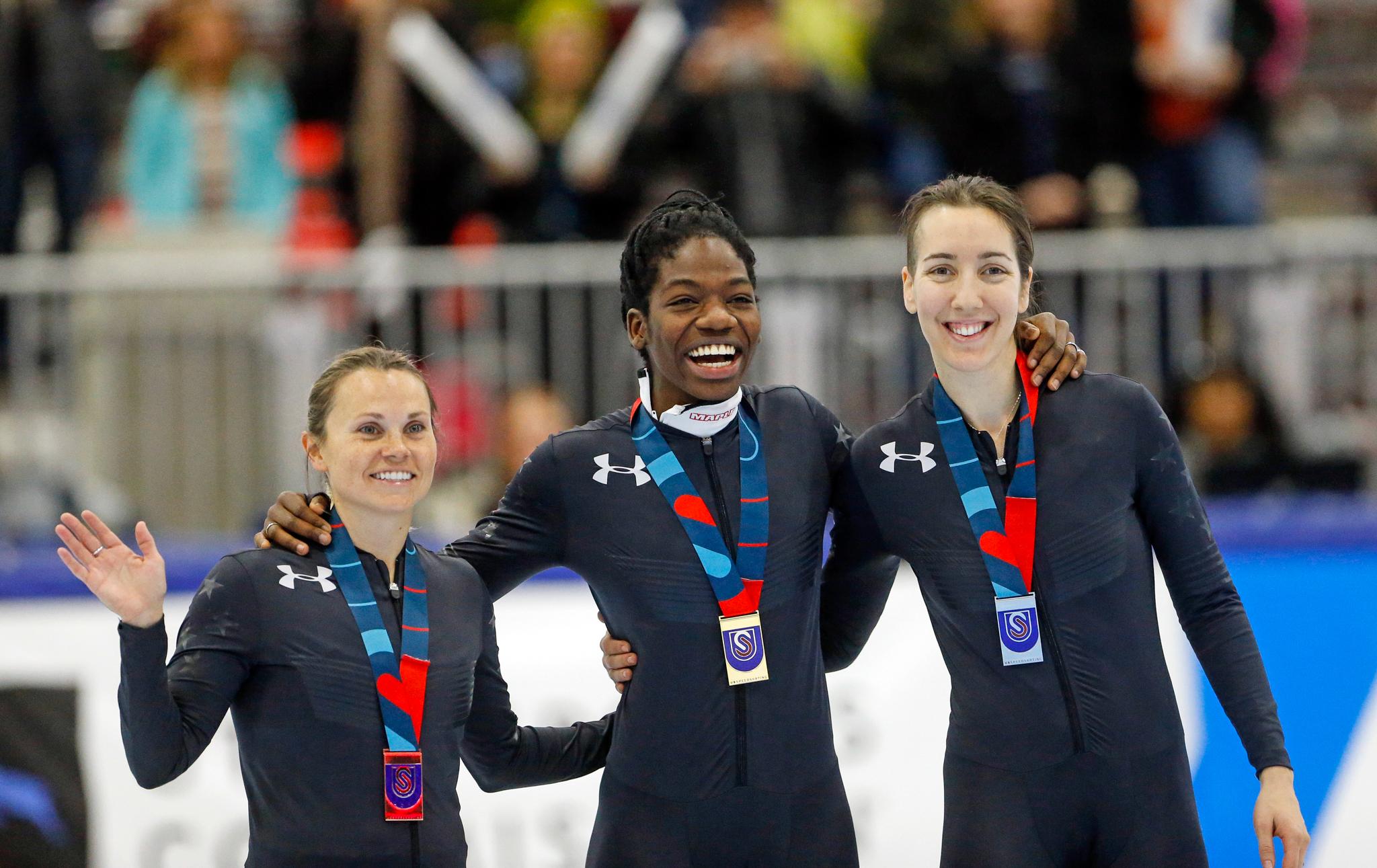 Three speedskaters wearing medals (© AP Images)