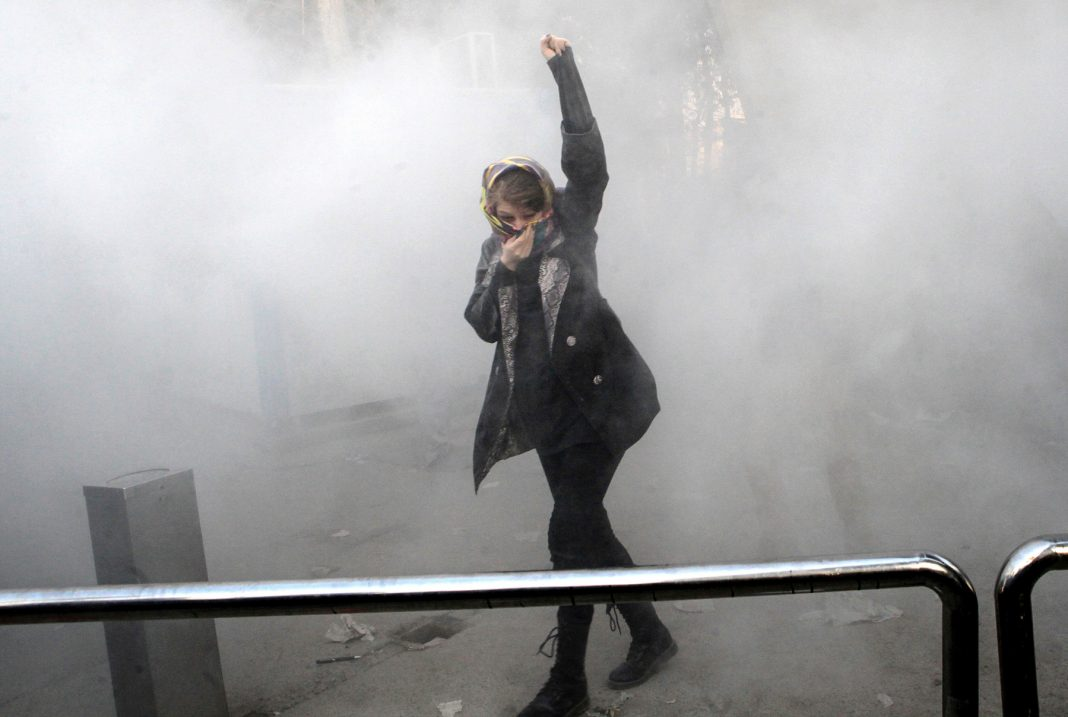 Une jeune femme, le poing levé et un foulard sur le nez et la bouche pour se protéger de la fumée (© AP Images)
