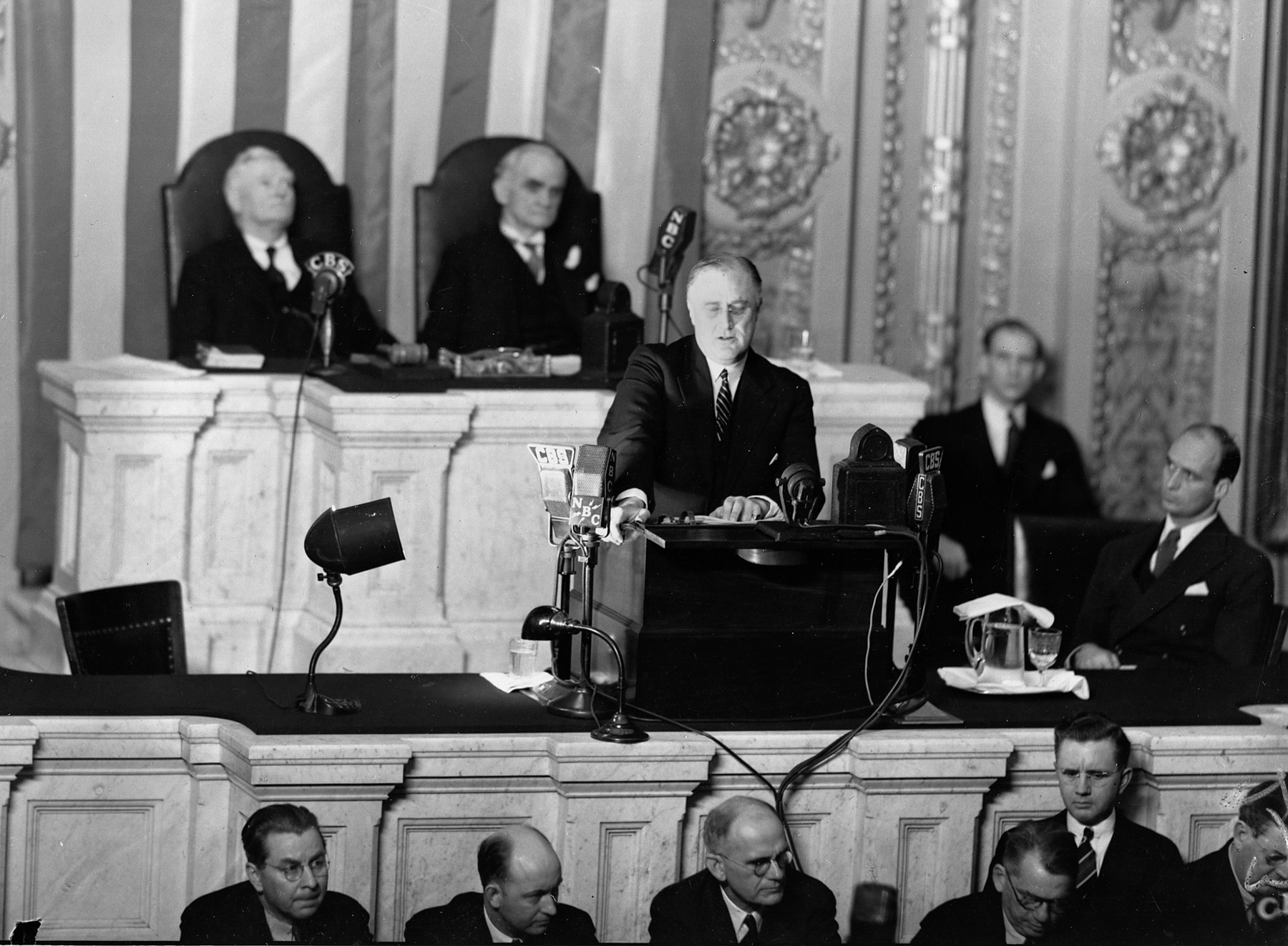 Franklin Roosevelt at lectern with officials seated around him (© AP Images)