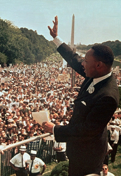 Martin Luther King Jr. waving to large crowd, Washington Monument in background (© AP Images)