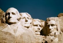 Four heads of presidents carved into the side of a mountain, Mount Rushmore (© AP Images)