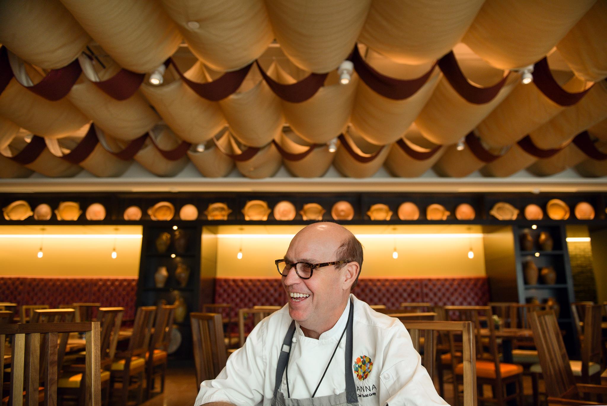 Smiling man sitting in restaurant (© Carol Guzy)