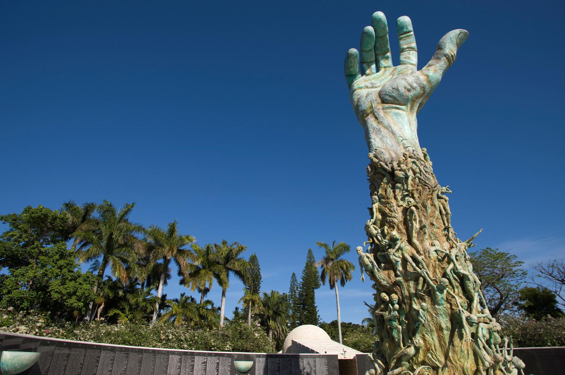 Sculpture d'un bras de géant tendu vers le ciel avec des centaines de personnes qui y sont accrochées (Alamy)