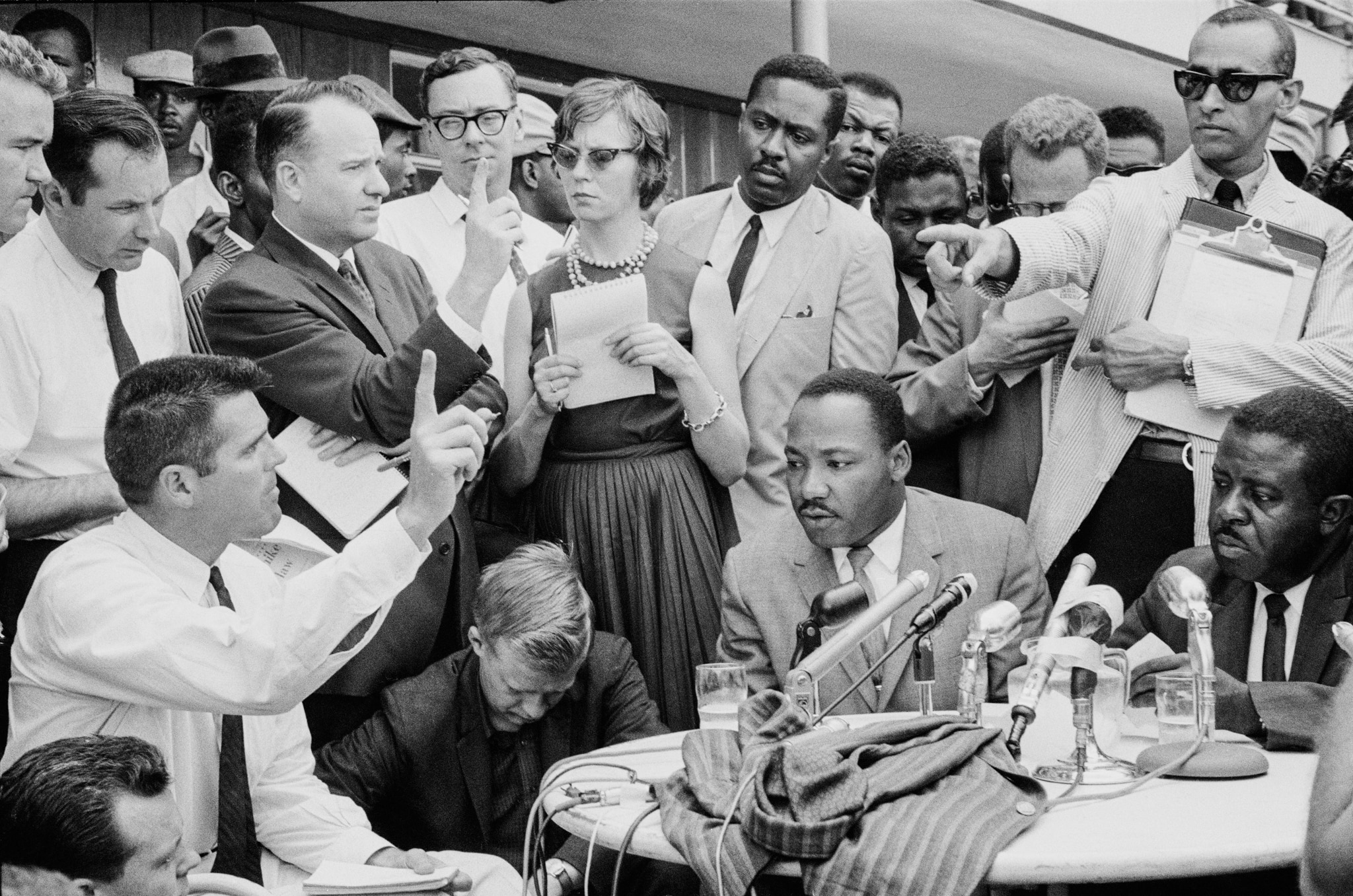 Martin Luther King Jr. seated at table, surrounded by people at press conference (© Ernst Haas/Hulton Archive/Getty Images)