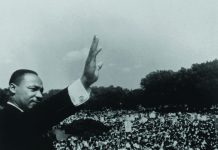 Martin Luther King le bras levé au ciel devant une immense foule (Francis Miller/Life Picture Collection/Getty Images)