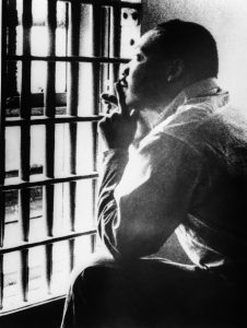 Martin Luther King Jr. looking out through jail bars (© Bettmann/Getty Images)