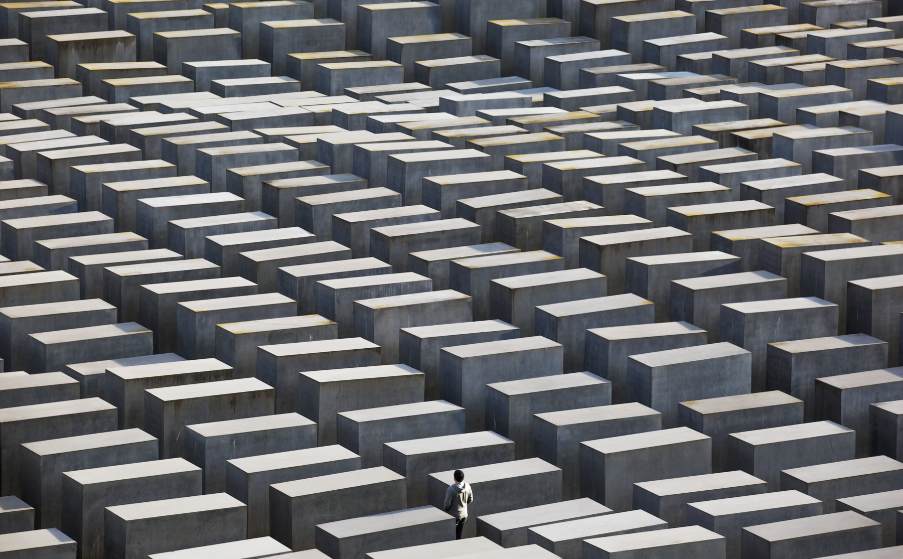 Un homme marchant entre des stèles en béton au Mémorial aux Juifs assassinés d'Europe, à Berlin (© Thomas Trutschel/Photothek via Getty Images)